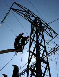overhead pylon - workers maintaining a safe distance from overhead electric cables